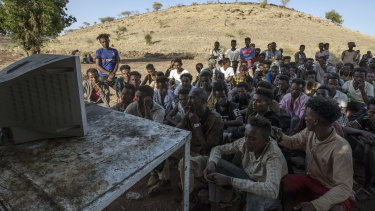 Tigranyan men who fled the conflict in Ethiopia's Tigray region, watch the news on a television, at Umm Rakouba refugee camp in Qadarif, eastern Sudan.