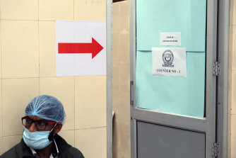 A healthcare worker waits outside a vaccination centre in New Delhi.