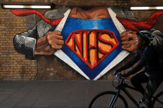A cyclist rides past an NHS mural in London.