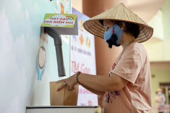 """A person wearing a protective mask collects rice from a """"rice ATM"""" at a distribution centre during a partial lockdown imposed due to the coronavirus in Ho Chi Minh City, Vietnam."""