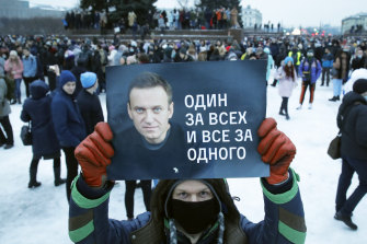 "A protester in St Petersburg on January 23 holds up a sign with a Alexei Navalny and the slogan ""One for all and all for one""."
