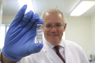 Prime Minister Scott Morrison holds up the AstraZeneca COVID-19 vaccine.
