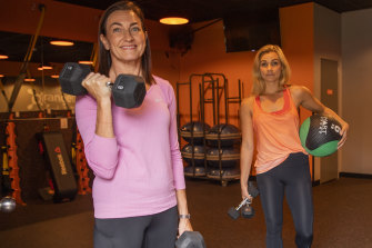 Rachael Looney (left) picking up dumbbells to take home from Orangetheory's Makenna Eide.