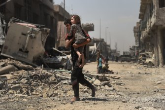 A young man runs barefoot carrying his sister as they escape from West Mosul.