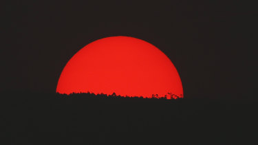 Tinted blood red by a thick cloud of smoke and pollution, the sun sets on the mountains above Mexico City on Monday.