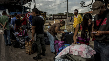 Venezuelans wait to register with immigration authorities after crossing the border into Pacaraima, Brazil.