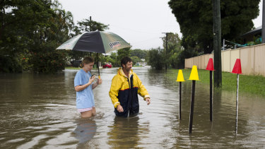 Local resident Paul Shafer and daughter Lily standing in floodwaters in Hermit Park, Townsville, on Saturday. Paul has been opening storm water drains near his house to reduce flooding, with the star pickets showing where the storm water cover has been removed.