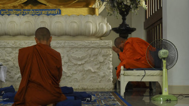 Dhammananda in prayer in front of a blue Buddha at the Songdhammakalyani Monastery.