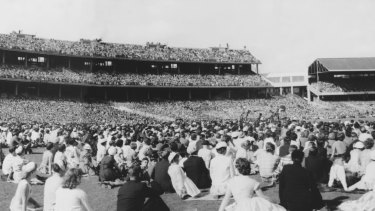 A crowd at the MCG in 1959 wait to hear Billy Graham preach the gospel.