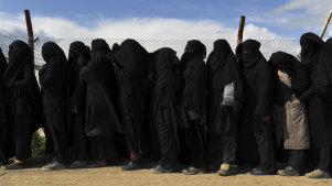 Foreign ISIS wives and children line up near the foreign section of Al Hawl camp to be taken to the shops.