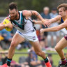 Powering on: Port Adelaide's Charlie Dixon (left) tries to brush off a tackle from Brisbane's Harris Andrews.