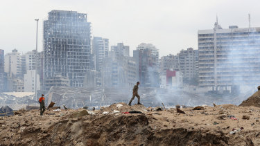 A soldier walks past the crater left by the devastating explosion at the Port of Beiriut.