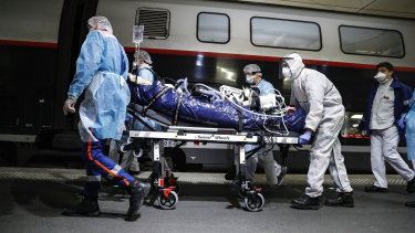 Medical staff transfer a patient infected with the coronavirus in Paris.