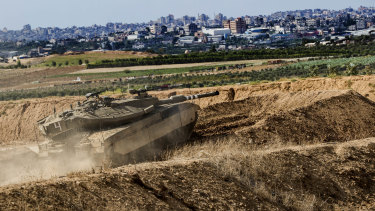 """Israeli tank takes a position at the Gaza Strip border, as Israel carried out a """"wide-scale"""" strike on Iranian targets in Syria."""
