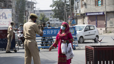 A Kashmiri woman requests a police officer to let her cross a street during curfew in Srinagar, Indian controlled Kashmir, on Tuesday.