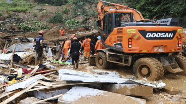 In this Aug. 3, 2020 photo, rescue workers search for survivors at a damaged house after a landslide caused by heavy rain in Gapyeong, South Korea. More than a dozen people including a few New Zealand citizens have died in landslides and floods caused by days of torrential rains that began Saturday, the Ministry of the Interior and Safety said Tuesday.