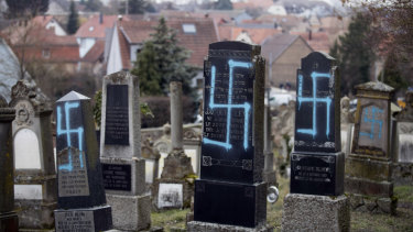 Vandalized tombs with tagged swastikas are pictured in the Jewish cemetery of Quatzenheim, eastern France.