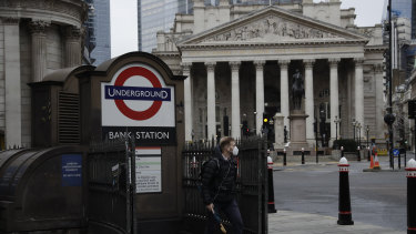 A man walks out of Bank underground train station backdropped by the Royal Exchange in the London.