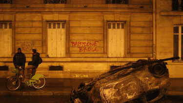 """A burned out car and the slogan, """"Babylon burns"""" in Paris on Sunday."""