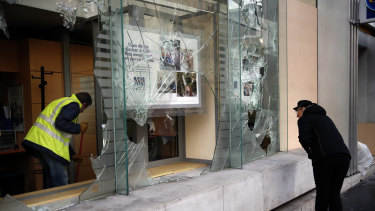 A worker clears debris in a bank as a man watches through smashed windows in Paris on Sunday.