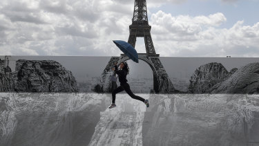 Culture in the air: a woman jumps in front of the Eiffel Tower where an exhibit has been installed. French President Emmanuel Macron is offering cash to stimulate young people's consumption of art, music, and even video games.
