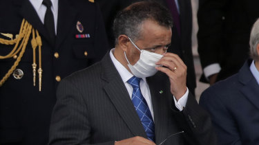 Director General of the World Health Organisation, Tedros Adhanom Ghebreyesus, adjusts a face mask as he attends the Bastille Day military parade, Tuesday, in Paris.
