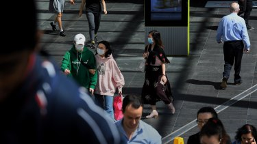 People with face masks walking along the street in Chatswood.