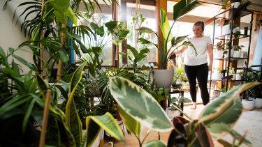 Rachel Okell waters one of 70 indoor plants at her home.