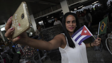 A Cuban doctor holding Brazilian and Cuban flags takes a selfie before she and other Cuban physicians return home at the airport in Brasilia.