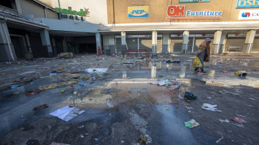 A young girl carrying groceries looted from a nearby shop, walks back home at Naledi shopping complex in Vosloorus, east of Johannesburg.