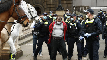 Police arrest a man at the anti-lockdown protest in Melbourne's CBD on Sunday.