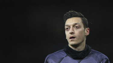 Arsenal's Mesut Ozil warms up prior the English Premier League soccer match between Arsenal and Manchester City, that was pulled off Chinese TV.