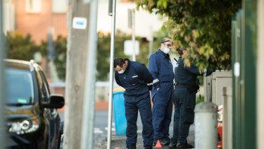 Forensic police inspect the scene in Walpole Street, Kew.
