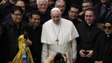 Pope Francis poses for a picture with priests during the weekly general audience at the Vatican on Wednesday.