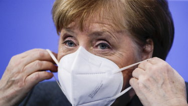 German Chancellor Angela Merkel puts on a face mask after a news conference on further coronavirus measures on Tuesday.