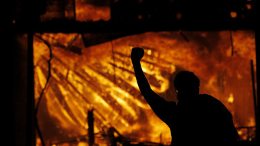 A protester gestures in front of the burning third precinct building of the Minneapolis Police Department on Thursday.