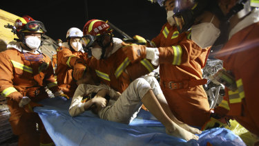 Rescuers place a boy pulled from the rubble of a collapsed hotel on a stretcher in Quanzhou, south-east China.