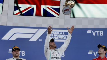 Cutting loose: Lewis Hamilton celebrates on the podium, as second-placed Valtteri Bottas (left) and third-placed Charles Leclerc (right) look on.