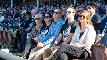 Raudonikis' wifeTrishBrown, far left, and family watch the service.