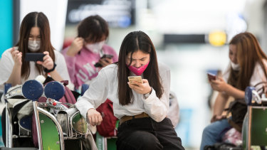 Travellers arrive at Melbourne Airport wearing face masks .