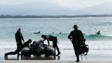 Police divers prepare to search water off Watego's Beach on Thursday.