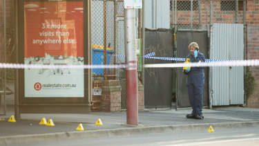 Police at a tram stop in Kew, near where a 59-year-old man was stabbed to death.