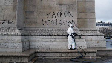 "A worker about to clean graffiti saying "" Macron resignation"" on the Arc de Triomphe."