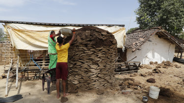 Villagers pile up cow dung to prepare cow dung cake, used as fuel,  at Ganeshpur village, Uttar Pradesh state, India.