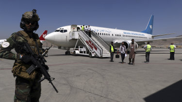 A Taliban soldier stands guard as passengers disembark on arrival from Kandahar, at Hamid Karzai International Airport in Kabul, Afghanistan, on Sunday.