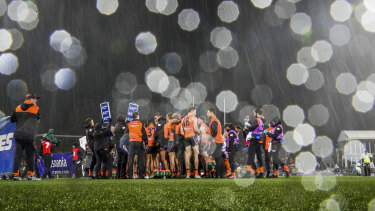 Snow falls on the ground during the game. between GWS and Hawthorn at Manuka Oval in Canberra on Friday night.