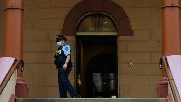 A masked officer at the entrance of NSW Parliament House.