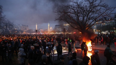 People gather in Place De La Nation as smoke rises from small fires that were lit at the end of a demonstration in Paris.