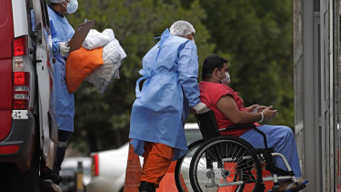 Healthcare workers push a patient suspected of having COVID-19 from an ambulance into a public hospital in Brasilia on the day the country passed 400,000 deaths from the disease.