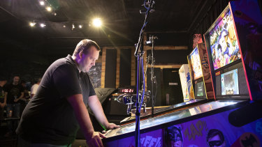 Richard Rhodes competes in the finals of the pinball championship at Belconnen.